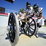 Wolf Pack defensive back Duke Williams, right and tight end Randy Horton touch the Fremont Cannon before the 2012 game at UNLV.