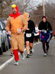 Steven Brown, of Arlington, Washington, rounds the last turn to complete the Turkey Trot Thursday morning. Runners began and finished at Notre Dame High School.
