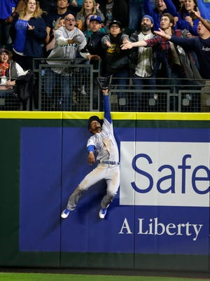Kansas City Royals right fielder Jarrod Dyson leaps, but can't catch a solo home run by Seattle Mariners' Seth Smith during the sixth inning of a baseball game, Friday, April 29, 2016, in Seattle.