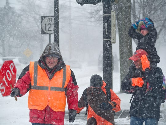 "Crossing Guard Bruce Rioux smiles and he helps Isabella Santor, Richard Woods and his son Wyatt Woods cross North Street in the Old North End on Jan. 27. ""Its a pain to walk in the blustery wind."" said Woods."