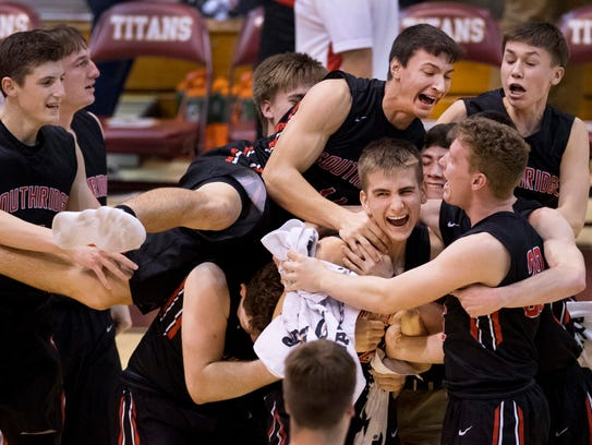Southridge's Garrett Voegerl (22) is mobbed by his teammates after making the game-winning shot against Gibson Southern.