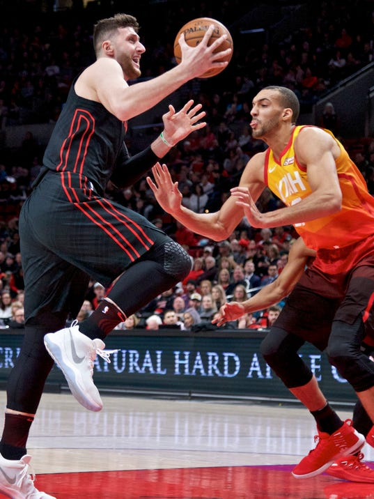 Portland Trail Blazers center Jusuf Nurkic, left, shoots over Utah Jazz center Rudy Gobert during the first half of an NBA basketball game in Portland, Ore., Sunday, Feb. 11, 2018. (AP Photo/Craig Mitchelldyer)