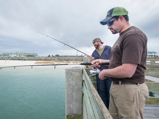 Brothers Matthew, left, and Chris Howell, of Knoxville, Tennessee, fish off the pier at Fort Pickens in Pensacola on Thursday, February 1, 2018.