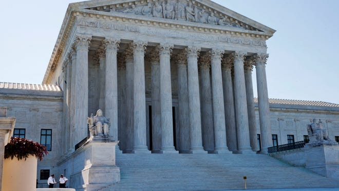 In this June 29, 2015, file photo, security guards stand outside of the U.S. Supreme Court in Washington, D.C.