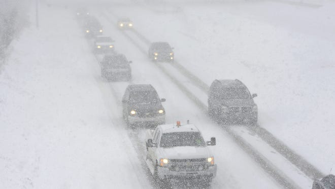 Traffic on the freeway in near white-out conditions.