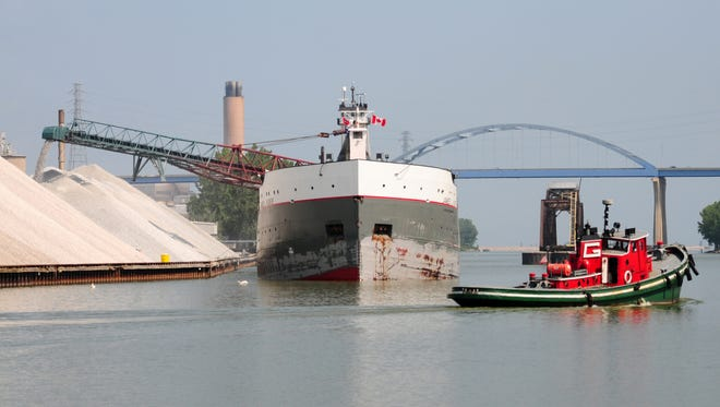 The tug, Texas, motors past the James L. Kuber unloading limestone at the Graymont terminal in Green Bay on July 31.