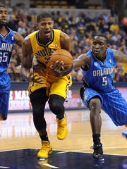 Pacers Paul George drives between Orlando's Victor