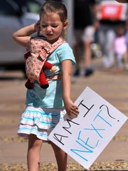 Caroline Macaluso, 4, carries a sign during the March
