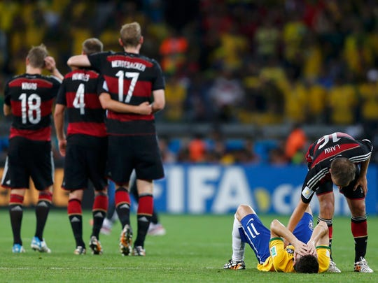 Germany's Philipp Lahm (R) consoles Brazil's Oscar after the 2014 World Cup semifinals between Brazil and Germany at the Mineirao stadium in Belo Horizonte July 8, 2014.