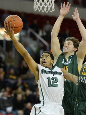 UW-Green Bay's Carrington Love (12) tries to lay up a shot past Wright State's Kendall Griffin (15) and Grant Benzinger (13) in the first half during Monday night's Horizon League game at the Resch Center in Ashwaubenon. Evan Siegle/Press-Gazette Media