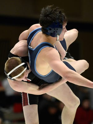At left, Pulaski's Jake Gille throws down Bay Port's Dylan Sundin in their 145-pound match during Thursday night's wrestling dual at Bay Port High School in Suamico. Gille won the match 7-4. Evan Siegle/Press-Gazette Media
