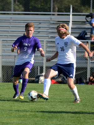Madison's Andy Carter keeps posession of the ball during Tuesday's game against Trinity Christian.