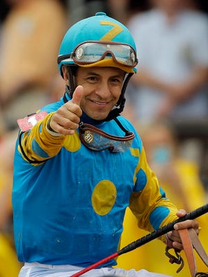 Jockey Victor Espinoza celebrates aboard American Pharoah after winning the 140th Preakness Stakes horse race at Pimlico Race Course.
