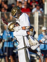 Salesianum's Michael Drake leaps into the arms of teammate