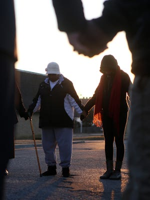 Mondarrius Miller's girlfriend Domique Maxwell, right, holds hands with Mary Weddle during a prayer circle before an anti-crime march at The Villages at Old Hickory apartment complex on Friday afternoon. Miller was killed on Jan. 12.