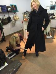 Kate Surmeier models the cashmere coat that she found at Bloom Designer Finds, while shop owner Ashley Steenhoven freshens it up.