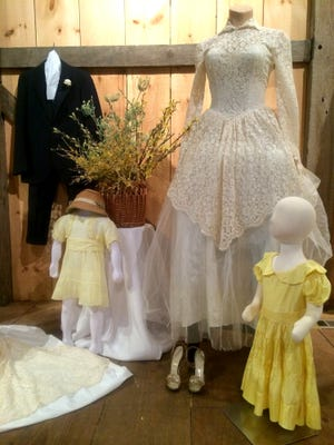 """Shown is the wedding dress of Nancy Meyers Pensinger, worn on August 9, 1953, when she married Robert """"Red"""" Pensinger.  To the right is the flower girl's dress that was worn by Nancy's little sister Brenda Meyers Denisar.  To the left of Nancy's dress is the flower girl's dress that Nancy wore at the wedding of her aunt and uncle, Mary Meyers and Ray Gibble, on January 1, 1937.  In the background is the blue pinstripe suit that Nancy's father, Noah Myers, wore on his wedding day in 1931."""