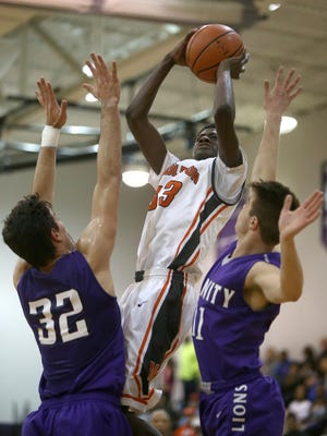 Middleton's Tylandrius Parks (33) puts a shot up over Trinity Christian Academy's Sergio Pagoaga (32) and Jake Morford (11) during the District 15-A title game at TCA on Tuesday, Feb. 23, 2016.