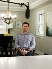 Troy Shafer sits in the dining room he restored at
