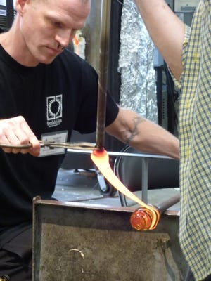 Artists Benjamin Mathes of Falls Church gets assistance from another artist with a dynamic piece. Over a dozen artists take turns demonstrating their craft during both days of the VA Hot Glass Festival.