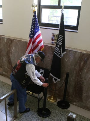 Rolling Thunder Tennessee VI President Jim Phelps works on the POW-MIA chair display inside the Madison County Courthouse on Friday morning.