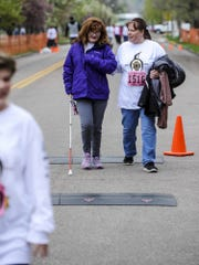 Crystal Case walks Megan Larocque, 16, across the 1 mile finish line during the 37th Annual Ice Breaker Sunday, April 24, 2016.