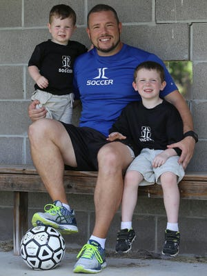 Jackson Christian coach Jeff Lean poses with his sons Elliott, left, and Liam.