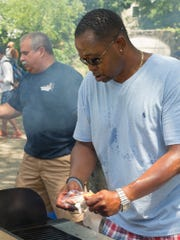 Dale Cooper of Ithaca, foreground, and Deputy Chief of Police Vincent Monticello cook Saturday afternoon at the Second Annual Ithaca Police Department Barbecue.