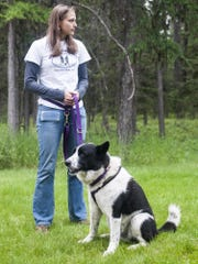 Kelsie Hay stands with Akela, a Karelian Bear Dog, outside of the West Glacier headquarters office.