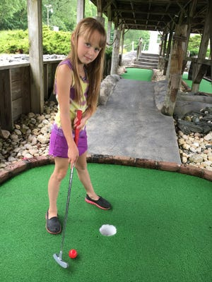 Chloe Miller from Palmyra practices her swing for SARCC's 17th annual minature golf tournament Saturday morning at Yogey's Putt 'N' Cream, 10 S. 22nd St., Lebanon.