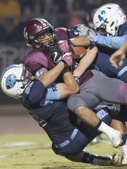 Redwood defenders tackle Mt. Whitney's Israel San Miguel in the annual Cowhide football game at Giant Chevrolet-Cadillac Mineral King Bowl on Friday, November 4, 2016.