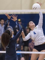 Exeter's Viviona Reveles hits against Redwood's Makayla Billups in Central Section Division II semifinal volleyball playoff game on Tuesday, November 8, 2016 in Exeter.