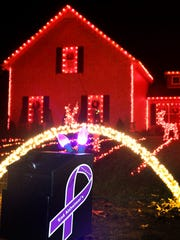 A box is decorated with purple lights is loacted in front of the home of Aaron and Shannon Grimes to accept donations for the Alzheimer's Association.