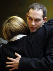Ryan Widmer hugs a supporter before opening statements during his 2011 murder trial in Warren County.