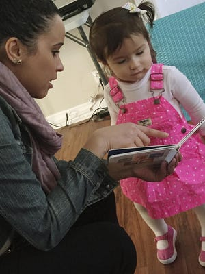 Stephanie Taveras, left, reads a book with 20-month-old Gracey Niebla, right, at the child's home in Providence, R.I.