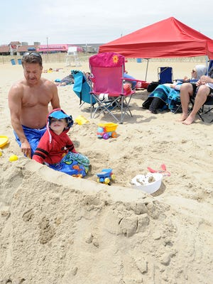 Mark Carnegie from Albany, New York with his grandson Spencer, 3, and family, work in the sand on Rehoboth Beach with their tent set up for protection from the sun.