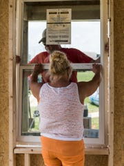Lowe's manager Sandra Simon (front) helps John Graupner (back) install a new window in a 20x20 room, which will be used for game officials and meetings at the Newman Softball fields in Henderson on Tuesday. The Lowe's crew started working at 7 a.m. continuing until late in the afternoon on Tuesday.