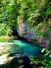 The cold, blue waters of Ha Ha Tonka Spring emerge from a towering rock bluff.