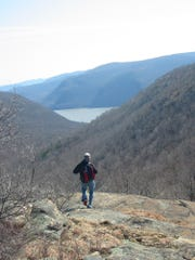 A hiker at Breakneck Ridge Trail with the Hudson River in the distance between Bull Hill (left) and the western part of Breakneck Ridge. East Hudson Highlands, NY State.