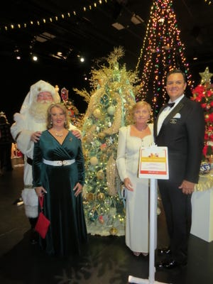 David Thomas, right, invited Mr. and Mrs. Santa Claus to join him and Marie Hintemyer to stand for this photograph in front of Dillard's Christmas tree.