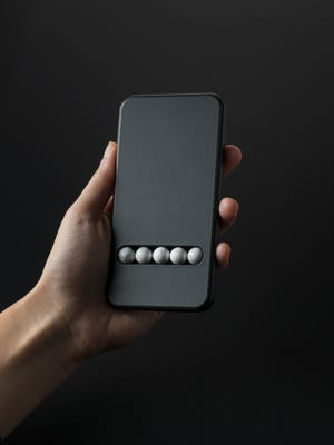 The Substitute Phone, which resembles a smartphone in size and shape, but features stone beads to simulate gestures such as swiping or tapping.