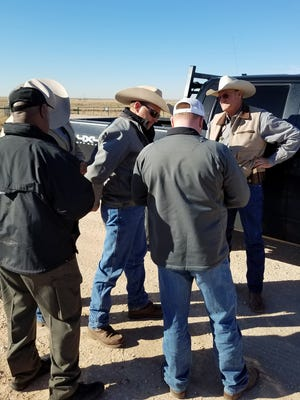 The suspect, Justin Tyler Greer, 36, is pictured being handed over to Tulare County Sheriff's Agricultural Crimes Detective Randy Gunderman, back to camera, from members of a Fugitive Task Force shortly after he was arrested in Tarzan, Texas.