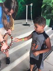 Braydon Edwards, 6, of Columbus, Ohio touches a snake