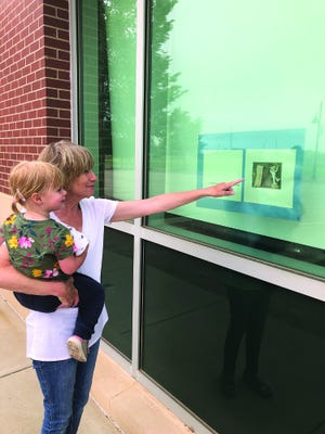 Lori Blackburn and Caroline Gamble view a page of the StoryWalk posted on a window at the Kiowa County Library in Greensburg.