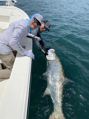 Captain Tommy Derringer and Tom Scott with a pretty tarpon caught behind a shrimp boat earlier in the week.