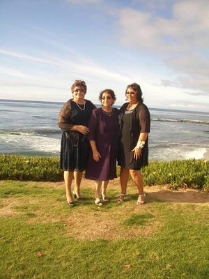 In this Oct. 23, 2010, photo ,Norma Kennedy, center, stands for a photo with her daughters, Diane Kennedy, left, and Cindy Mohr in La Jolla, Calif., during a family wedding. All three women died of COVID-19.