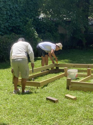 Topeka High Jobs for America's Graduates-Kansas career specialist Carlos Kelly, left, and JAG-K student Tylan Alejos construct an urban garden in Topeka.
