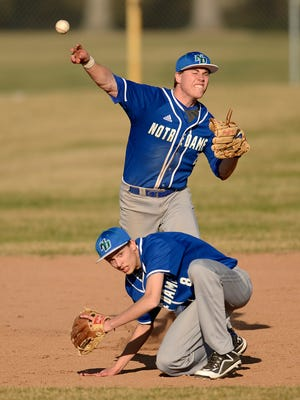 Green Bay Notre Dame's Charlie Rotherham (2) makes a throw over teammate Chris Wolcanski (8) during Thursday's baseball game against Green Bay Southwest at VandenPlas Field in Green Bay.