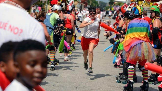 "Runners make their way through the finish line Saturday during the sixth annual ""Fiesta de San Fermin en Pensacola"" Running of the Bulls."
