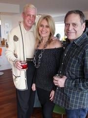 Interior designer Jamie Gibbs, left, poses with a cocktail